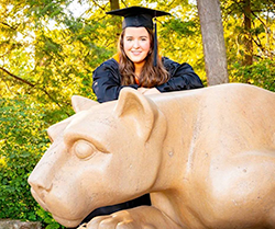 A woman wearing a blue graduation cap and gown poses for a photo on the Penn State Nittany Lion, a sculpture of a mountain lion.