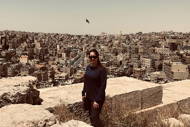 A woman wearing dark clothing stands at an overlook of a city with hundreds of buildings behind her.
