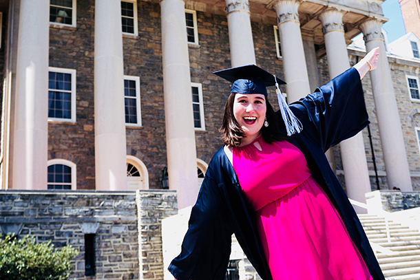 White woman in pink dress and blue graduation cap and gown smiles in front of a brick building